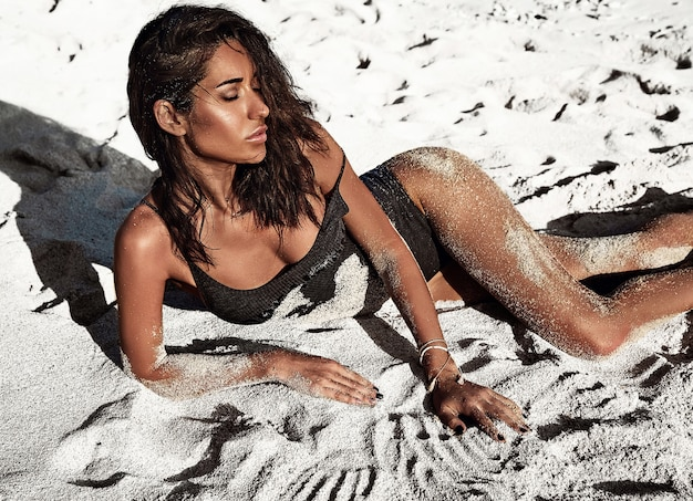 Ritratto del modello di bella donna caucasica preso il sole con i capelli lunghi scuri in costume da bagno sdraiato sulla spiaggia estiva con sabbia bianca Foto Gratuite