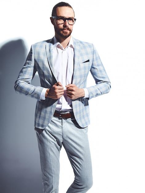 Ritratto del modello di uomo d'affari alla moda hipster alla moda bello vestito in elegante abito azzurro in bicchieri su bianco Foto Gratuite