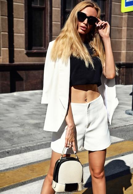 Ritratto del modello moderno della donna di affari di modo sexy in vestito bianco che posa sui precedenti della via con la borsa Foto Gratuite