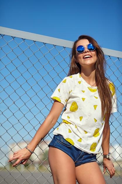 Ritratto del modello sorridente bello alla moda della giovane donna di fascino pazzo divertente in abbigliamento casual di estate dei pantaloni a vita bassa luminosi che posa nella via dietro la griglia e il cielo blu del ferro Foto Gratuite