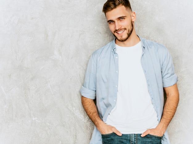 Ritratto del modello sorridente bello del giovane che indossa i vestiti casuali della camicia. posa alla moda dell'uomo di modo Foto Gratuite