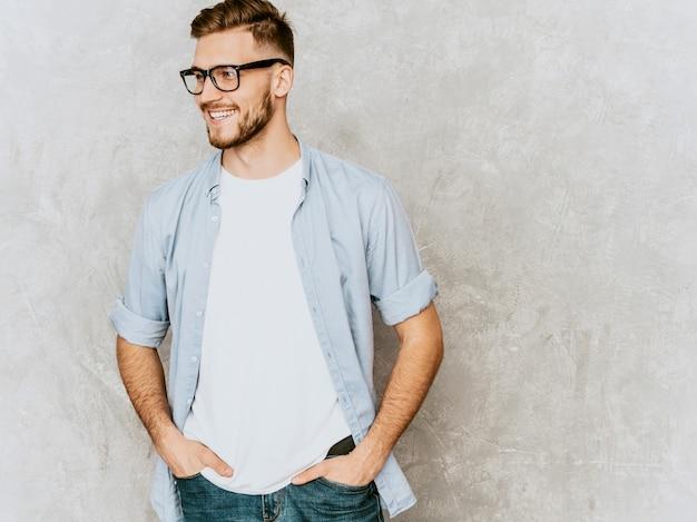 Ritratto del modello sorridente bello del giovane che indossa i vestiti casuali della camicia. uomo alla moda di modo che posa in occhiali Foto Gratuite