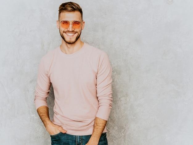 Ritratto del modello sorridente bello del giovane che indossa i vestiti casuali di rosa di estate. uomo alla moda di modo che posa in occhiali da sole rotondi Foto Gratuite