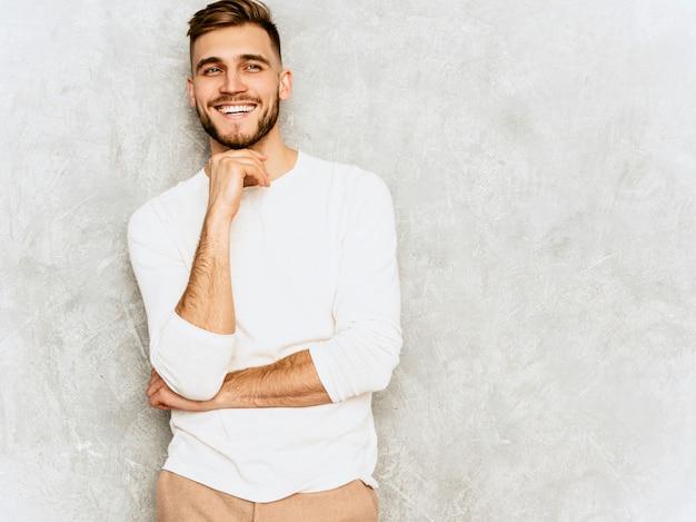 Ritratto del modello sorridente bello dell'uomo d'affari dei pantaloni a vita bassa che indossa i vestiti bianchi casuali di estate ... toccando il suo mento e pensiero Foto Gratuite