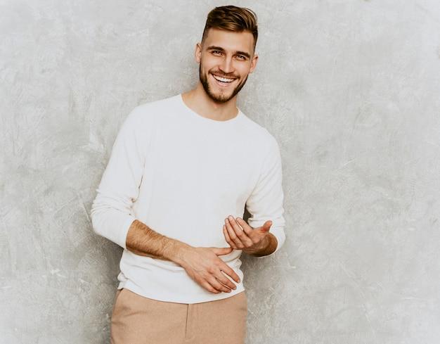 Ritratto del modello sorridente bello dell'uomo d'affari dei pantaloni a vita bassa che indossa i vestiti bianchi casuali di estate. Foto Gratuite