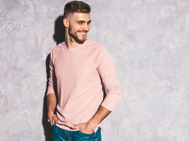 Ritratto del modello sorridente bello dell'uomo d'affari dei pantaloni a vita bassa che indossa i vestiti casuali di rosa di estate. Foto Gratuite