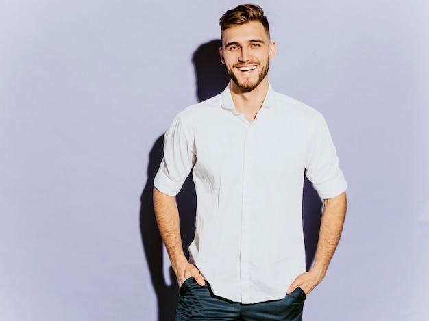 Ritratto del modello sorridente bello dell'uomo d'affari dei pantaloni a vita bassa che indossa l'abbigliamento casual. Foto Gratuite