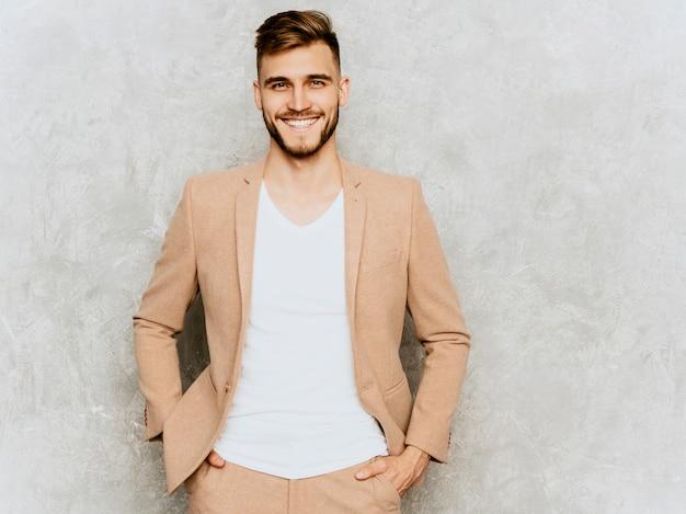 Ritratto del modello sorridente bello dell'uomo d'affari dei pantaloni a vita bassa che indossa vestito beige casuale. Foto Gratuite