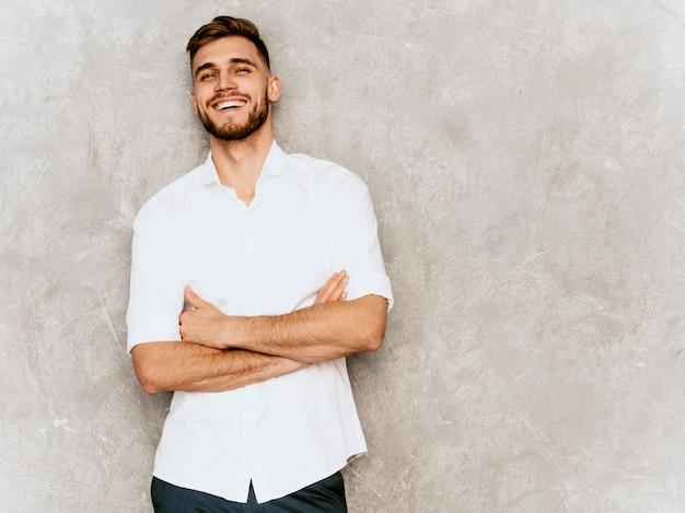 Ritratto del modello sorridente bello dell'uomo d'affari dei pantaloni a vita bassa che porta la camicia bianca casuale di estate. Foto Gratuite