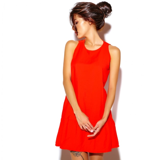 Ritratto del modello sveglio della giovane donna di modo in un vestito rosso su una parete bianca Foto Gratuite
