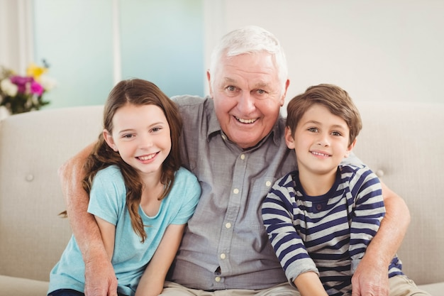 Ritratto del nonno e dei nipoti che si siedono insieme sul sofà in salone Foto Premium