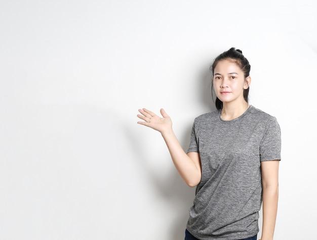 Ritratto del presentatore asiatico della donna su fondo bianco, donna asiatica che indica lo spazio della copia, bella ragazza tailandese. Foto Premium