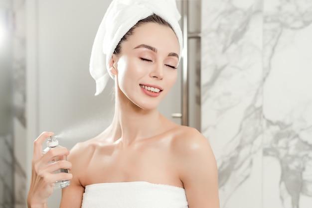 Ritratto del primo piano con profumo che spruzza sul collo di giovane bella donna avvolta in asciugamani nel bagno. concetto di bellezza e cura della pelle Foto Premium