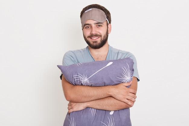 Ritratto del primo piano del cuscino grigio abbracciante sorridente del maschio barbuto, posante contro la parete bianca dopo essersi svegliato, indossando una maschera di sonno Foto Gratuite