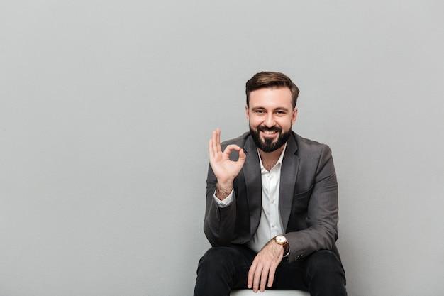 Ritratto del primo piano del tipo allegro che mostra segno giusto mentre riposando sulla sedia in ufficio che è soddisfatto, isolato sopra grey Foto Gratuite