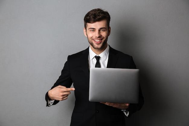 Ritratto del primo piano dell'uomo d'affari allegro che indica con il dito sul suo computer portatile, Foto Gratuite