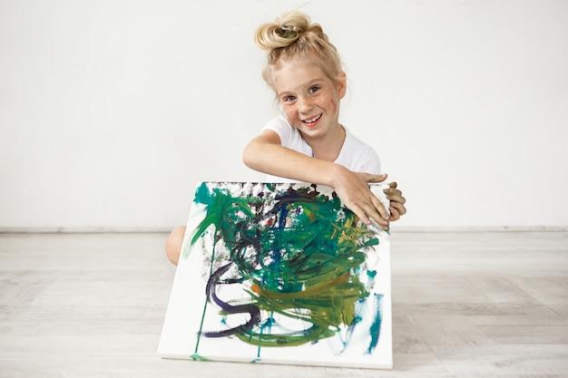 Ritratto del primo piano della bambina europea bionda con il panino e le lentiggini dei capelli che sorridono con tutti i suoi denti. tenendo in ginocchio l'immagine che ha dipinto per i suoi genitori, sentendosi orgogliosa di se stessa. persone a Foto Gratuite