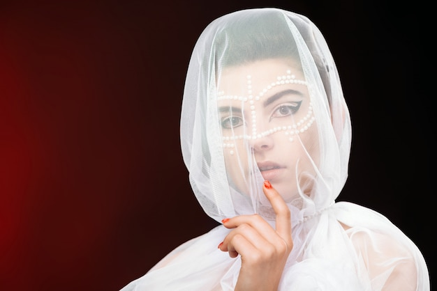 Ritratto del primo piano della donna del charmig con il velo sul suo fronte e Foto Premium