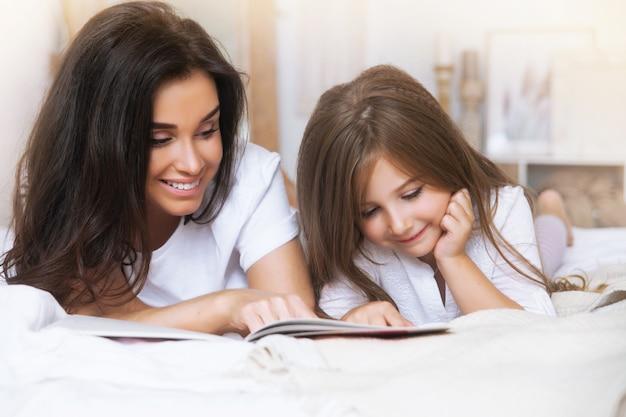 Ritratto del primo piano della madre e della figlia sorridenti che leggono a letto nelle prime ore del mattino nello scandinavo bianco Foto Premium