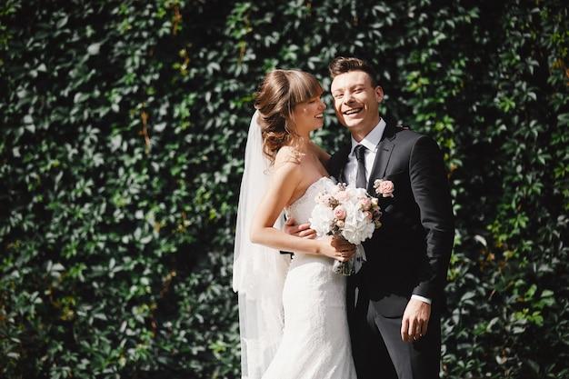 Ritratto del primo piano della sposa e dello sposo di nozze con la posa del mazzo. coppia di sposi, happy newlywed donna e uomo che abbraccia. sposa e sposo Foto Premium