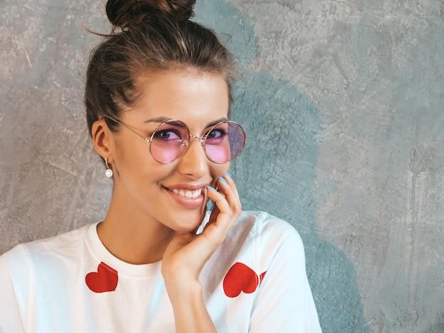 Ritratto del primo piano di giovane bello sguardo sorridente della donna. ragazza alla moda in abito bianco estivo casual e occhiali da sole. Foto Gratuite