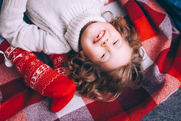 Ritratto del primo piano di un ragazzo dai capelli ricci, il ragazzo si trova su un plaid rosso sul pavimento in un maglione che sorride senza denti guardando il telaio. Foto Premium