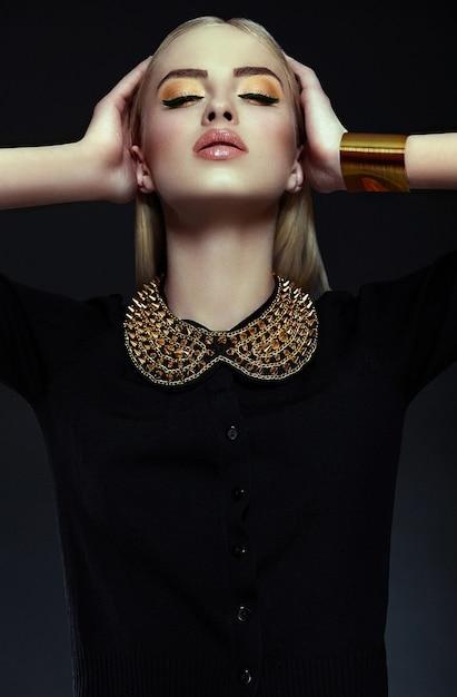 Ritratto del primo piano look.glamor di alta moda di bello modello di giovane donna bionda alla moda sexy con trucco giallo brillante con pelle pulita perfetta con gioielli in oro in panno nero Foto Gratuite