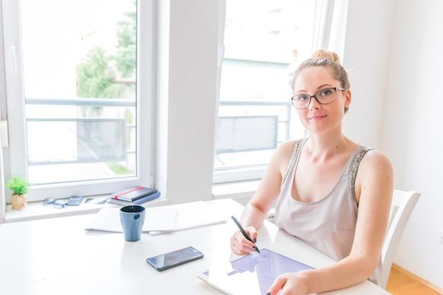 Ritratto del progettista femminile grafico astuto facendo uso della compressa digitale grafica nel luogo di lavoro Foto Gratuite