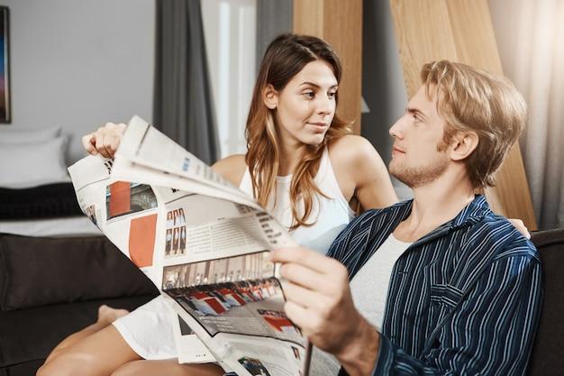 Ritratto del ragazzo barbuto bello essere distratto dalla fidanzata durante la lettura del giornale a casa. la donna vuole attirare la sua attenzione e gli dice qualcosa di sorprendente. Foto Gratuite