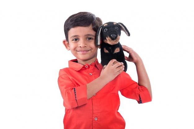 Ritratto del ragazzo che gioca con il suo animale domestico di peluche sulla parete bianca Foto Premium