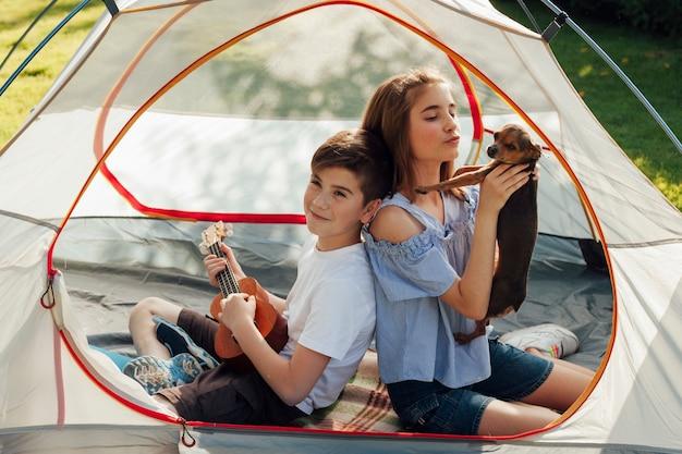 Ritratto del ragazzo e della ragazza che si siedono in tenda con il cane e le ukulele della tenuta Foto Gratuite