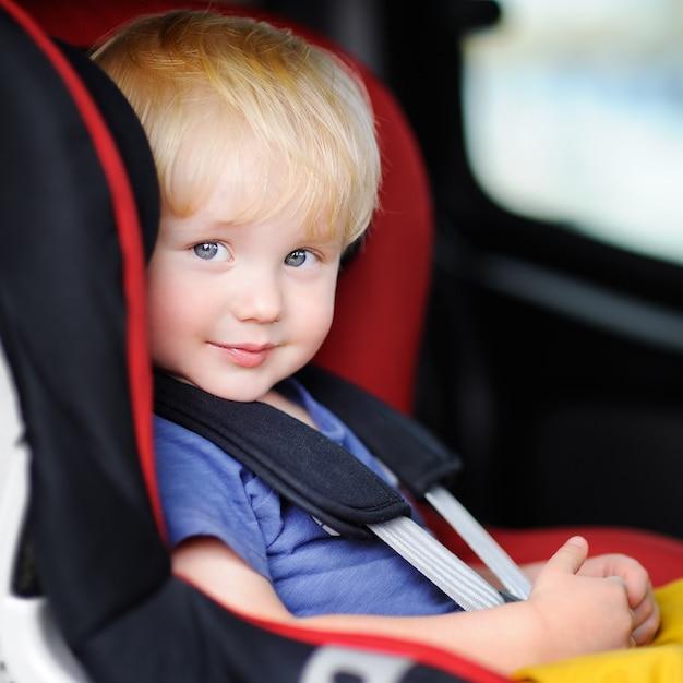 Ritratto del ragazzo grazioso del bambino che si siede nella sede di automobile Foto Premium