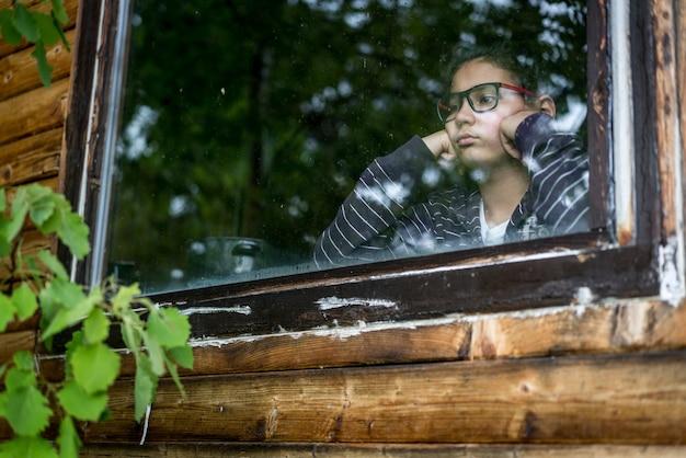 Ritratto del ragazzo guardando attraverso la finestra Foto Premium
