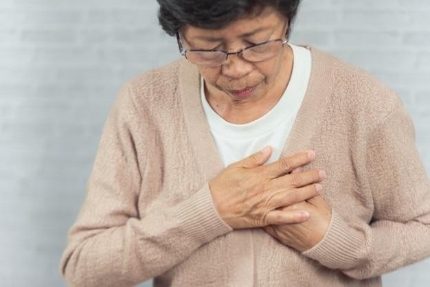 Ritratto del seno della tenuta della donna anziana a causa dell'infarto del cuore su gray Foto Premium