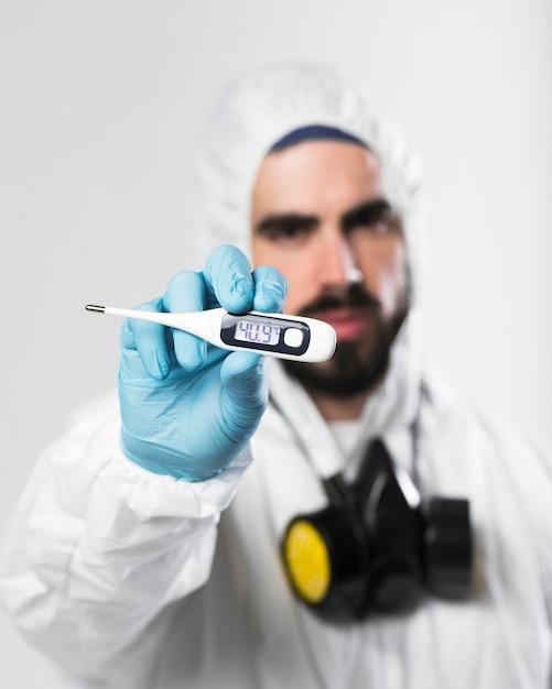 Ritratto del termometro della tenuta del maschio adulto Foto Gratuite