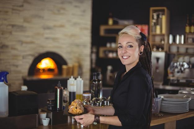 Ritratto del vassoio della tenuta della cameriera di bar di muffin al contatore Foto Gratuite