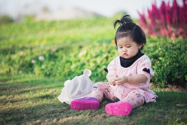 Ritratto del viaggio sveglio del bambino al giardino di fiori Foto Premium