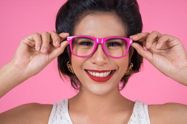 Ritratto dell'azione della donna di modo con gli occhiali da sole Foto Gratuite