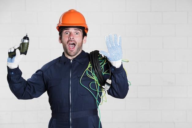 Ritratto dell'elettricista maschio sorpreso che esamina macchina fotografica con la bocca aperta Foto Gratuite
