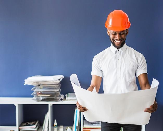 Ritratto dell'ingegnere maschio che porta un elmetto protettivo arancione che esamina cianografia Foto Gratuite