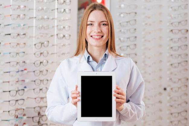 Ritratto dell'optometrista femminile amichevole che mostra il modello della compressa Foto Gratuite