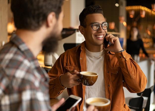 Ritratto dell'uomo afroamericano sorridente che parla sul telefono cellulare. vita bassa amici che bevono caffè insieme, comunicazione, risate, utilizzando smartphone, seduti in caffetteria. concetto di pausa caffè Foto Premium