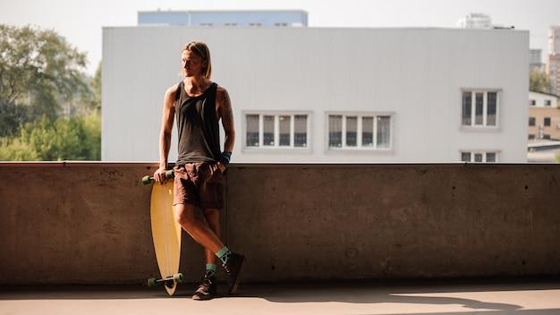 Ritratto dell'uomo che sta con un longboard e distogliere lo sguardo Foto Premium