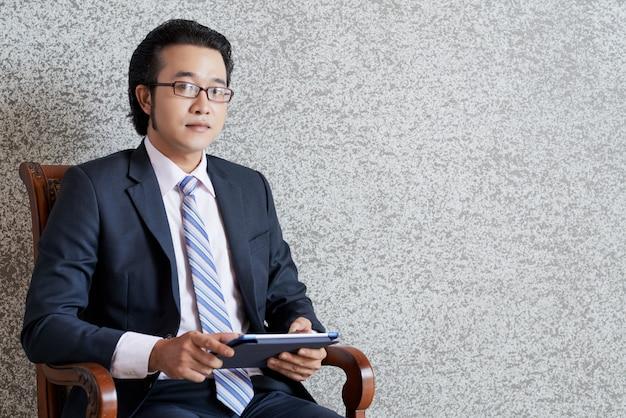 Ritratto dell'uomo d'affari che si siede con la compressa in poltrona e che esamina diritto la macchina fotografica Foto Gratuite
