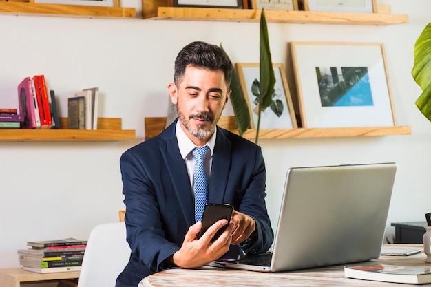 Ritratto dell'uomo d'affari con il computer portatile sulla sua tavola facendo uso del telefono cellulare Foto Gratuite