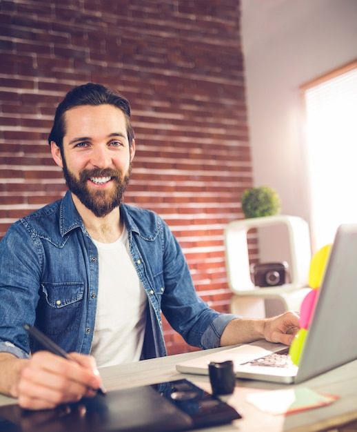 Ritratto dell'uomo d'affari sorridente facendo uso della tavola e del computer portatile grafici Foto Premium