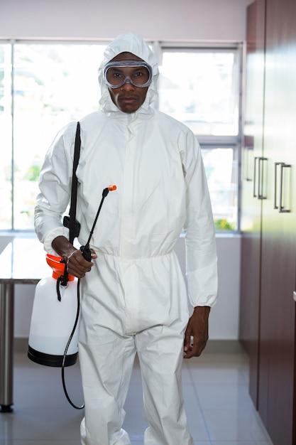 Ritratto dell'uomo di controllo dei parassiti che sta con lo spruzzatore dell'insetticida Foto Premium