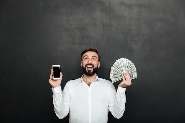 Ritratto dell'uomo estatico che esprime i guadagni online con la tenuta dei lotti della valuta e dello smartphone del dollaro dei soldi, isolato sopra grigio scuro Foto Gratuite