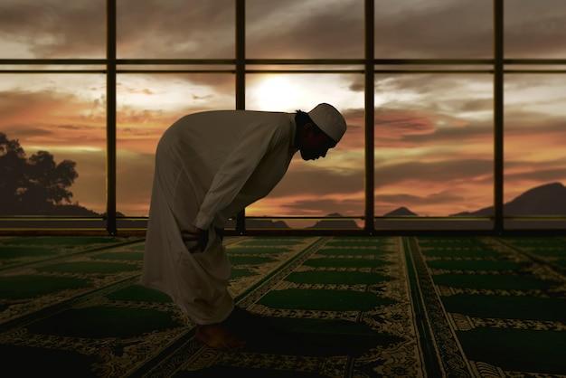 Ritratto dell'uomo musulmano asiatico che prega sulla moschea Foto Premium