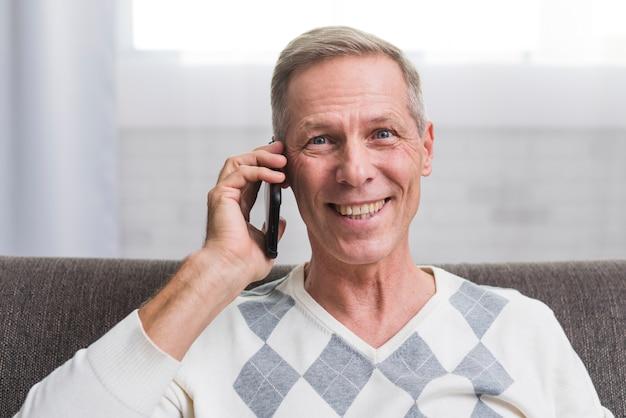 Ritratto dell'uomo sorridente che parla al telefono Foto Gratuite